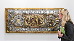 "© Licensed to London News Pictures. 05/10/2018. LONDON, UK. A visitor views ""The American Dollar Bill II"" by Argentinian artist Elisa Insua.  The artwork comprises found objects gold and silver objects. Opening day of The Other Art Fair, presented by Saatchi Art, which runs until 7 October in Bloomsbury.  The fair, which coincides with Frieze Week, is a collection of artworks by independent and emerging artists handpicked by a committee of art world experts.  Visitors and art buyers have the opportunity to meet the artists presenting their work at the fair. Photo credit: Stephen Chung/LNP"