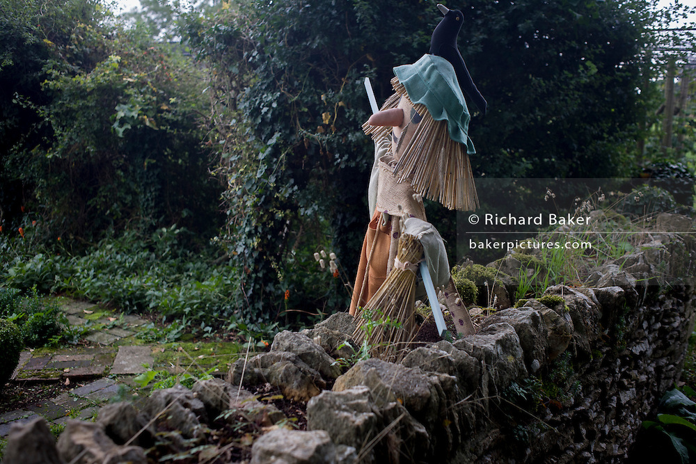 A scarecrow guards crops by a Gloucestershire country garden dry stone wall