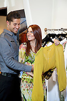 Happy young couple selecting a dress together in fashion boutique