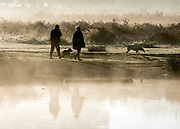 © Licensed to London News Pictures. 06/11/2014. Richmond, UK. People walk next to a misty pond.  People and animals during a frosty start to the day on 6th November 2014. Temperature fell across the country overnight. Photo credit : Stephen Simpson/LNP
