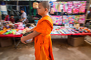 06 APRIL 2013 - SANPATONG, CHIANG MAI, THAILAND:   Novice monks walk through the market in Sanpatong, Chiang Mai, Thailand on their alms rounds. The buffalo market in Sanpatong (also spelled San Patong) started as a weekly gathering of farmers and traders buying and selling water buffalo, the iconic beast of burden in Southeast Asia, more than 60 years ago and has grown into one of the largest weekend markets in northern Thailand. Buffalo and cattle are still a main focus of the market, but traders also buy and sell fighting cocks, food, clothes, home brew and patent medicines.        PHOTO BY JACK KURTZ