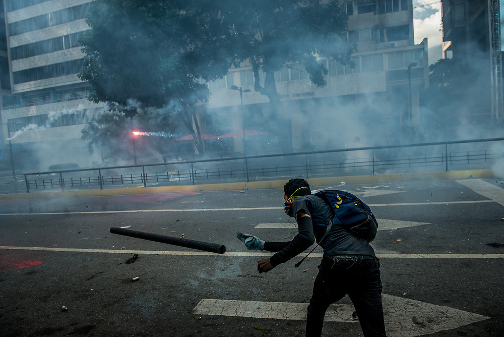 CARACAS, VENEZUELA - MAY 20, 2017:  Anti-government protesters clash with members of the National Police who responded by heavily tear gassing and firing rubber bullets and buckshot at them. The streets of Caracas and other cities across Venezuela have been filled with tens of thousands of demonstrators for nearly 100 days of massive protests, held since April 1st. Protesters are enraged at the government for becoming an increasingly repressive, authoritarian regime that has delayed elections, used armed government loyalist to threaten dissidents, called for the Constitution to be re-written to favor them, jailed and tortured protesters and members of the political opposition, and whose corruption and failed economic policy has caused the current economic crisis that has led to widespread food and medicine shortages across the country.  Independent local media report nearly 100 people have been killed during protests and protest-related riots and looting.  The government currently only officially reports 75 deaths.  Over 2,000 people have been injured, and over 3,000 protesters have been detained by authorities.  PHOTO: Meridith Kohut