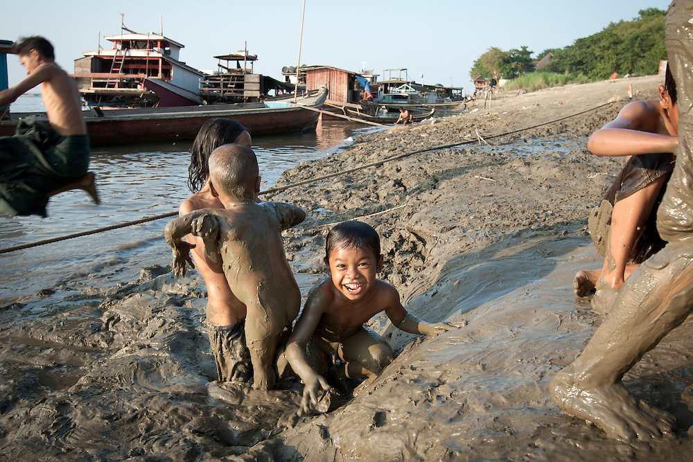 Kids slide down a slope of mud on the bank of Irrawaddy River in Mandalay in cenrtal Myanmar.