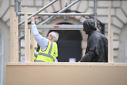 © Licensed to London News Pictures. 12/06/2020. London, UK. Workmen erect a barrier around a statue of Thomas Guy at Guys Hospital in London , ahead of a Black Lives Matter demonstration In Parliament Square, central London. Black Lives Matter have called for the removal of statures from throughout the UK of historical characters involved in the salve trade, following the death of George Floyd in the U. S. A . Photo credit: Ben Cawthra/LNP