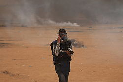 May 4, 2018 - Journalists covering the Great March of Return demonstrations east of Khan Yunis, near the Gaza Strip border with Israel, are directly targeted by tear gas canisters fired by the Israeli army. In spite of wearing clothes clearly marked with the word PRESS, which identify them as journalists and camera operators, Palestinian journalists have been deliberately targeted by Israeli snipers since the beginning of the Great March of Return protests. The Great March of Return is a series of mass protests along the Israel-Gaza border which began on March 30th to call for right to return for Palestinian refugees and their descendants to their ancestral lands in what is now Israel, and to demand the lift of the Israeli blockade on the Gaza Strip (Credit Image: © Ahmad Hasaballah/IMAGESLIVE via ZUMA Wire)