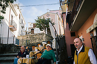 """PISCIOTTA, ITALY - 22 APRIL 2018: Men are seen here in front of a cafe in Pisciotta, Italy, on April 22nd 2018.<br /> <br /> Former restaurant owners Donatella Marino and her husband Vittorio Rimbaldo have spent the recent years preparing and selling salted anchovies, called alici di menaica, to a growing market thanks to a boost in visibility from the non-profit Slow Food.  The ancient Menaica technique is named after the nets they use brought by the Greeks wherever they settled in the Mediterranean. Their process epitomizes the concept of slow food, and involves a nightly excursion with the special, loose nets that are built to catch only the larger swimmers. The fresh, red anchovies are immediately cleaned and brined seaside, then placed in terracotta pots in between layers of salt, to rest for three months before they're aged to perfection.While modern law requires them to use PVC containers for preserving, the government recently granted them permission to use up to 10 chestnut wood barrels for salting in the traditional manner. The barrels are """"washed"""" in the sea for 2-3 days before they're packed with anchovies and sea salt and set aside to cure for 90 days. The alici are then sold in round terracotta containers, evoking the traditional vessels that families once used to preserve their personal supply.<br /> <br /> Unlike conventional nets with holes of about one centimeter, the menaica, with holes of about one and half centimeters, lets smaller anchovies easily swim through. The point may be to concentrate on bigger specimens, but the net also prevents overfishing."""