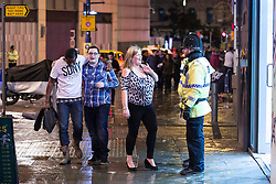 """© Licensed to London News Pictures . 20/12/2014 . Manchester , UK . People on Withy Grove . """" Mad Friday """" revellers out in the rain and cold in Manchester . Mad Friday is typically the busiest day of the year for emergency services , taking place on the last Friday before Christmas when office Christmas parties and Christmas revellers enjoy a night out .  Photo credit : Joel Goodman/LNP"""
