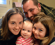 SELLERSVILLE, PA -  MARCH 7:  Emma Davies (C), 1 year old, poses in the living room with her father Jeremy Davies, mother Lisa Davies (L) and her sister Lily (R), 6, March 7, 2014 in Sellersville, Pennsylvania. Emma Davies is suffering from a rare hematological disease. She will be getting a bone marrow transplant from her older sister. With bills stacking up, a friend of the Davies family has set up an online fundraiser to help.(Photo by William Thomas Cain/Cain Images)