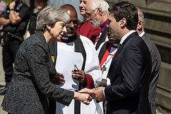 © Licensed to London News Pictures . 22/05/2018 . Manchester , UK . Prime Minister THERESA MAY is greeted by dignitaries , including Bishop DAVID WALKER  JOHN SENTAMU, SIR RICHARD LEESE and ANDY BURNHAM (shaking hands), at Manchester Cathedral ahead of a Service of Remembrance on the first anniversary of the Manchester Arena bombing . On the evening of 22nd May 2017 , Salman Abedi murdered 22 people and seriously injured dozens more , when he exploded a bomb in the  foyer of the Manchester Arena as concert-goers were leaving an Ariana Grande gig . Photo credit : Joel Goodman/LNP