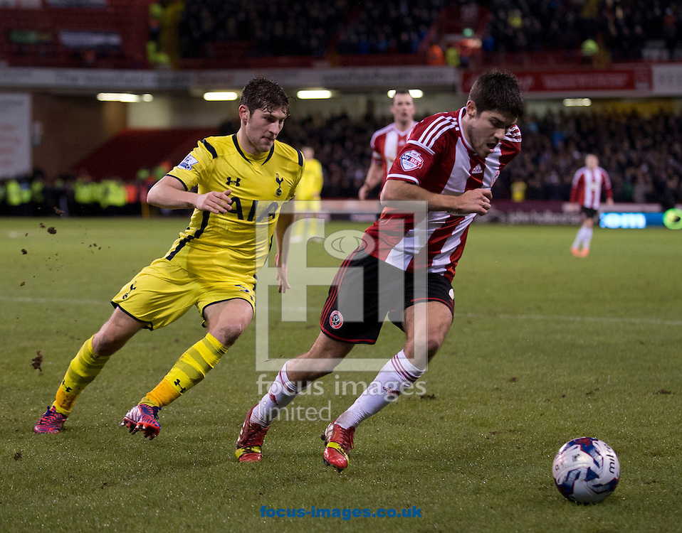 Ryan Flynn of Sheffield United (right) is closed down by Ben Davies of Tottenham Hotspur during the Capital One Cup match at Bramall Lane, Sheffield<br /> Picture by Russell Hart/Focus Images Ltd 07791 688 420<br /> 28/01/2015
