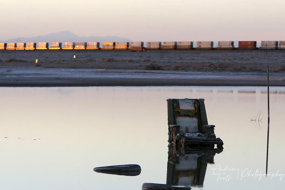 A train is lit by the sinking sun as an abandoned lounge chair sits in a lagoon next to the Salton Sea.