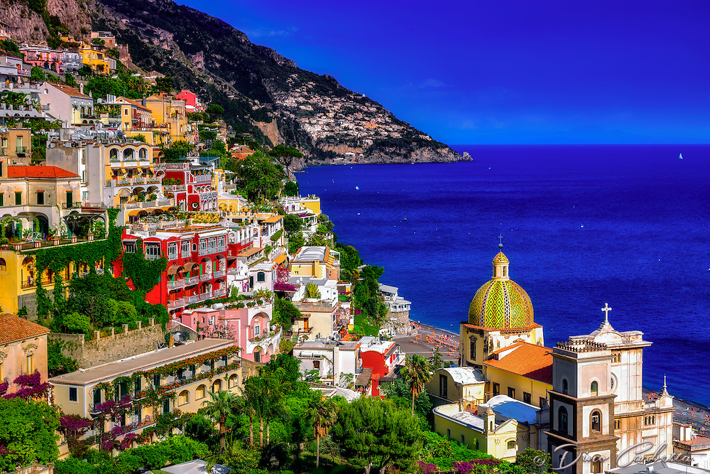 """""""The church of Santa Maria Assunta guards the coast of Positano""""…<br /> <br /> I never ventured to attempt many photos in the hot daylight sun of Italy; however, as the sun dropped down behind the cliffs of Positano in early evening…the lighting on the picturesque Amalfi village brought out the depth of color and highlighted the plush vegetation.  Around 5:00pm, I positioned the camera at the edge of the opposing cliff to frame this image allowing the colors to derive their true spectrum of light and power.  The focal point of most views of Positano is the church of Santa Maria Assunta.  The colorful dome is made of majolica tiles which are very prominent on the Amalfi Coast, and the church contains a thirteenth-century Byzantine icon of the legendary Black Madonna."""
