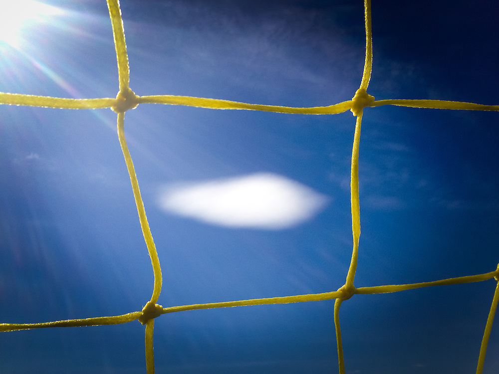 Cloud seen through a soccer goal net