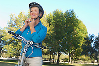 Senior woman fixing bicycle helmet