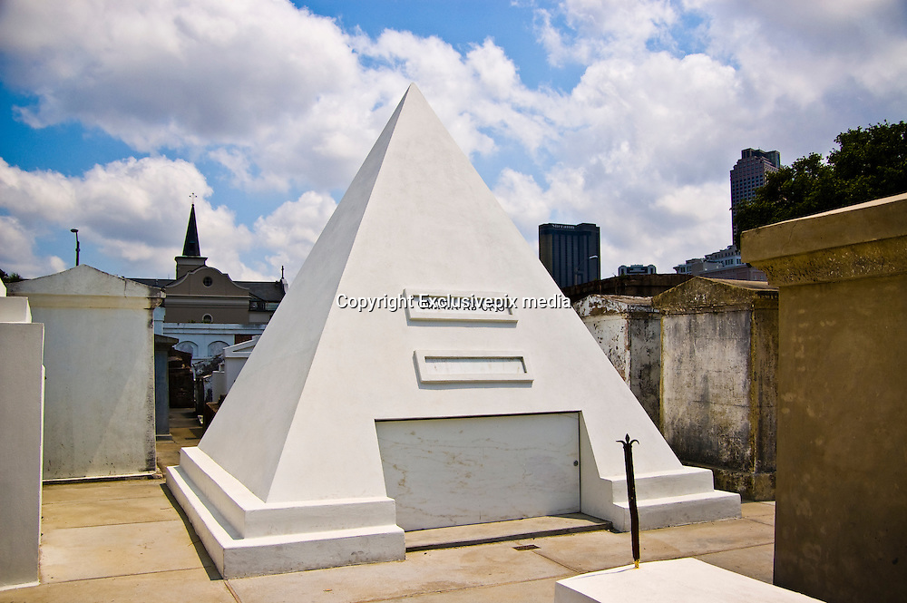 """The Pyramid Tomb of Nicholas Cage<br /> <br /> In 2010 Nicholas Cage purchased the last two plots in New Orleans' thickly populated St. Louis Cemetery No. 1. He had built on it a nine-foot-tall cement pyramid mausoleum, apparently for his future self.<br /> <br /> Saint Louis Cemetery is a two-hundred-year-old cemetery located in New Orleans, in Louisiana, that holds the remains of some of the city's most famous personalities including the voodoo Queen Marie Laveau. <br /> <br /> Some say that Cage's love of Voodoo motivated him to locate his tomb in the same ancient cemetery as Marie Laveau, the Voodoo Queen. The pyramid stands, stark and white and out-of-place among the surrounding graves, which are stained with centuries of New Orleans' grime and mold. Its only embellishment is a line of creepy lip prints, apparently left by adoring fans.<br /> <br /> While there is no doubt, the pyramid was chosen by the actor to be his final resting place, Nicolas Cage himself has never made a public declaration as to why he bought the pyramid-shaped tomb. Some speculate that the actor prescribes to the beliefs of the illuminati, others attempt to make a weak connection to the picture of a pyramid that appeared on the poster of the movie """"National Treasure"""" in which Nicholas Cage acted. There is even a wild theory that the pyramid is full of gold and cash that the actor is trying to shelter.<br /> <br /> Public opinion is divided. Purists hate Cage's pyramid, tour guides ridicule him and New Orleans locals are furious that he was even able to obtain a plot the size of four ordinary burial plots in the cramped graveyard.<br /> ©Exclusivepix media"""