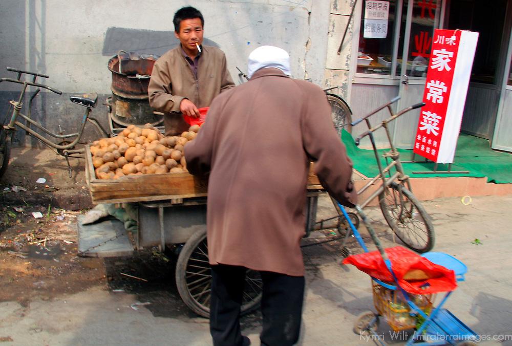 Asia, China, Beijing.  Smoking vegetable vendor in Beijing Hutongs.