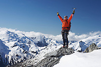 Mountain climber with arms raised on top of mountain peak
