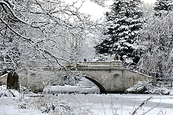© Licensed to London News Pictures. 10/02/2012, London, UK. A man walks across The Classic Bridge built for the 5th Duke of Devonshire. People enjoy the snow in the grounds of Chiswick House in West London today 10 February 2012. Chiswick House, undergoing restoration,  is the first and one of the finest examples of neo-Palladian design in England.  Inspired by the architecture of ancient Rome and 16th Century Italy, the third Earl of Burlington built the house as a homage to Renaissance architect Palladio.The cold weather across the UK is set to continue over the weekend.  Photo credit : Stephen Simpson/LNP