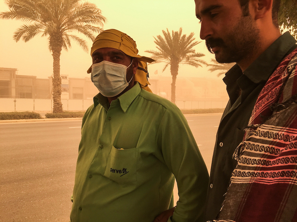 DUBAI, UAE — APRIL 2, 2015: Workers in a sandstorm **IPHONE**
