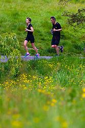 A couple enjoy a bank holiday Sunday run amongst the wild flowers on Hampstead heath in London. London, May 26 2019.