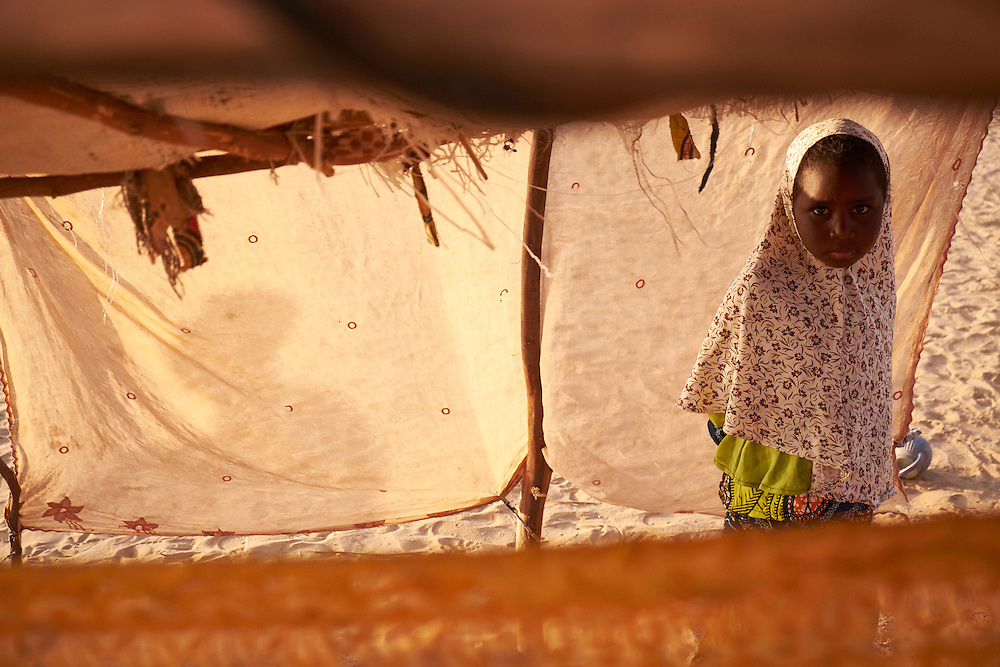 A girl in a shelter at a camp of displaced people in the neighbourhood of Chateau, Diffa, Niger on February 12, 2016. The girls family of four generations fled their village in Nigeria which was threatened of being attacked by Boko Haram. Having lost everything they have no intention of returning. The camp is mixed between displaced people from Niger, Nigeria and Chad. They have fled attacks by the militant group Boko Haram on their villages and it's ongoing conflicts with the armies of each country. Caritas undertook a distribution of mosquito nets, cooking pots, sleeping covers, hygiene kits, clothes and cash transfers to the displaced. 228 households received support from Caritas among an estimated 1500 households in the  vicinity of Chateau. There is still great need. There is no school system in place for the children and the housing is not adequate for many as more people arrive each day escaping hostilities.