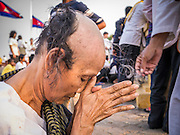 """31 JANUARY 2013 - PHNOM PENH, CAMBODIA: A Cambodian woman has her head shaved while mourning the death of former Cambodian King Norodom Sihanouk. In Cambodia, the spouse and the children mourn the death of their husband or father by shaving their heads, and many Cambodian women have shaved their heads recently because Sihanouk was revered as the father of the nation. Norodom Sihanouk (31 October 1922- 15 October 2012) was the King of Cambodia from 1941 to 1955 and again from 1993 to 2004. He was the effective ruler of Cambodia from 1953 to 1970. After his second abdication in 2004, he was given the honorific of """"The King-Father of Cambodia."""" Sihanouk served two terms as king, two as sovereign prince, one as president, two as prime minister, as well as numerous positions as leader of various governments-in-exile. He served as puppet head of state for the Khmer Rouge government in 1975-1976. Most of these positions were only honorific, including the last position as constitutional king of Cambodia. Sihanouk's actual period of effective rule over Cambodia was from 9 November 1953, when Cambodia gained its independence from France, until 18 March 1970, when General Lon Nol and the National Assembly deposed him. Upon his final abdication, the Cambodian throne council appointed Norodom Sihamoni, one of Sihanouk's sons, as the new king. Sihanouk died in Beijing, China, where he was receiving medical care, on Oct. 15, 2012. His funeral procession, which will wind through Phnom Penh is Friday, Feb.1 and his cremation is on Feb. 4, 2013. Over a million people are expected to attend the service.     PHOTO BY JACK KURTZ"""