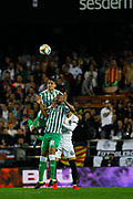 Marc Bartra (left) defender for Real Betis, jumps for an air ball against other players and grabs his team mate William Carvalho from the head