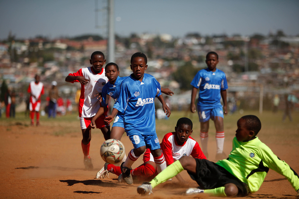World Cup fever hits Alexandra township. Children from Red Roses football club train in the kit of their favourite world cup team. Many of the team members are HIV/Aids orphans and live in child headed households. The daily training schedule and weekly matches are a welcome addition to lives facing many challenges. Poverty is high in Alexandra township which is a short distance from the wealthy world of Sandton, Northern Johannesburg. South Africa..Pictures by Zute & demelza Lightfoot www.lightfootphoto.com.+27(0)715957308 zutelightfoot@yahoo.co.uk