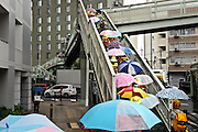 little school children with bright colored umbrellas using a cross over bridge Kyoto Japan
