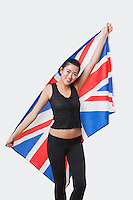Portrait of smiling young woman holding British flag over white background