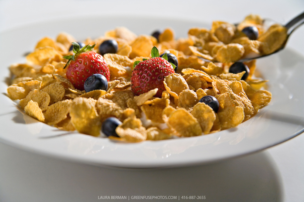 A bowl of corn flakes breakfast cereal with strawberries, blueberries and milk