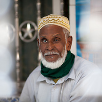 A muslim man with one false eye sits inside a mosque in the historic old city of Dhaka in Bangladesh