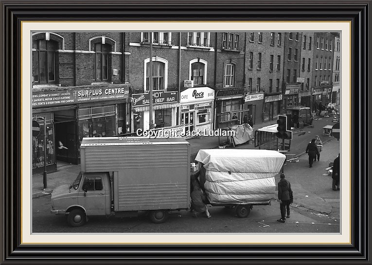 View of brick lane market from junction with bethnal green road finishing up for the daySeries of Black and White pictures Depicting Brick Lane Market London,  2 feb 1984<br /> Series of 7 Black and White Photographes Depicting Brick Lane Market London,  2 feb 1984<br /> A2/A3 Museum-quality Archival signed Framed Print (Limited Edition of 25) From Series of 7 Limited Edition (25) Large Framed Prints A3 Shot on film neg Black and White pictures Depicting Brick Lane Market London, 2 feb 1984 Photographer Jack Ludlam<br /> £1,200