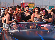 A group of young girls, dressed in 50's style sitting in a convertible Hotroad with two blokes, Viva Las Vegas Festival, Las Vegas, USA 2006.