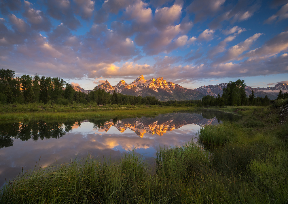 Sunrise refelction of the Tetons and pretty clouds at Schwabacher Landing, Grand Teton National Park, Wyoming