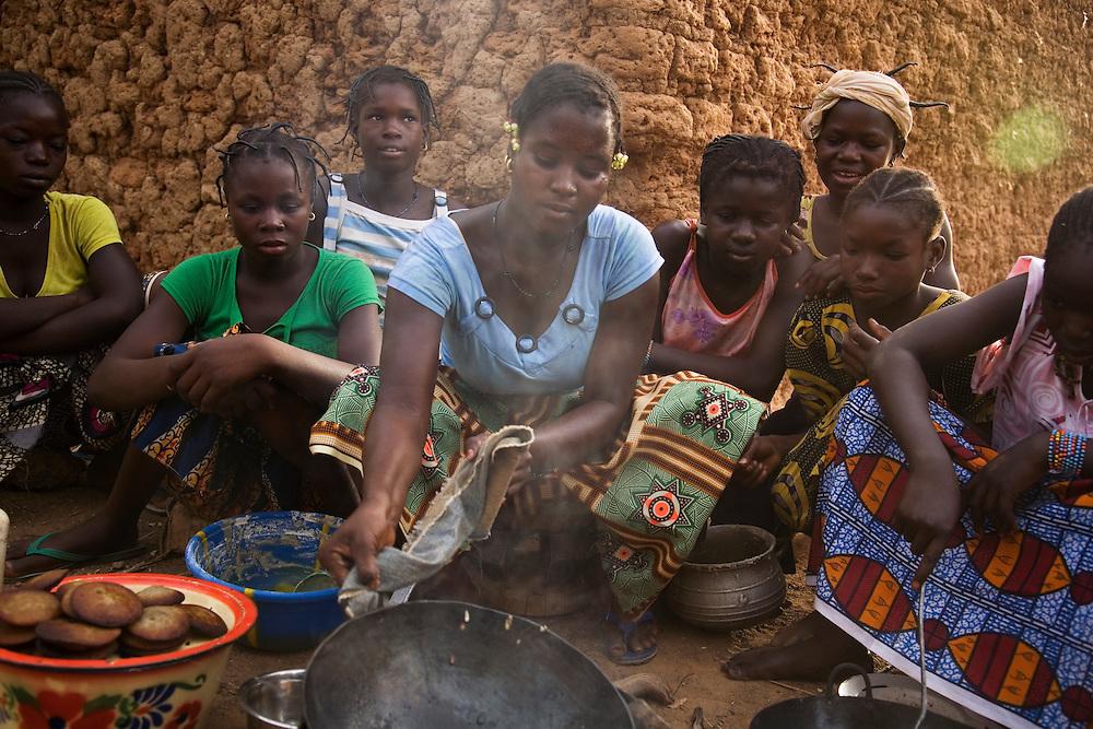 women in Nimbou cook fat cakes. No model release.