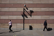 Businessmen walk below a CCTV camera with the shadow of a traffic camera on the wall of a modern office building in the City of London, the capital's financial district.
