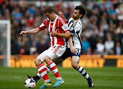 West Bromwich Albion's Claudio Yacob and Stoke City's Robert Huth battle for the ball - Photo mandatory by-line: Matt Bunn/JMP - Tel: Mobile: 07966 386802 19/10/2013 - SPORT - FOOTBALL - Britannia Stadium - Stoke-On-Trent - Stoke City V West Brom - Barclays Premier League