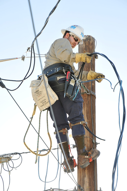 Tucson Electric Power lineman starts connecting 200 amp service to my house.