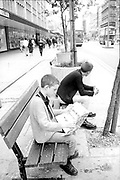 Neville Watson and Dean Spencer Sitting on Bench Reading Paper, Oxford Circus, London.  1980s.