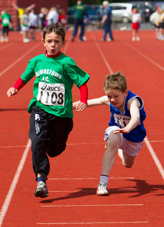 Meath Athletics track & field championships at Claremount stadium 16th May 2010<br /> Boys u-12 final<br /> Niall Moynaghan (Cushinstown AC) crosses the finish line in 2nd place while Shane Smith (Tara) loses his footing and stumbles.<br /> Photo: David Mullen / www.cyberimages.net