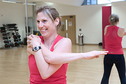 Woman stretching her arms and back in an aerobics class at her sports leisure centre,