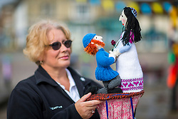 © Licensed to London News Pictures. 13/05/2018. Thirsk UK. Emma Feely of the Thirsk Yarn Bombers with her woollen creation of Prince Harry & Megan Markle. The Thirsk Yarn bombers have decorated the town centre of Thirsk in North Yorkshire this morning with Prince Harry & Megan Markle wedding related woollen creations to celebrate the upcoming royal wedding at the weekend. Photo credit: Andrew McCaren/LNP