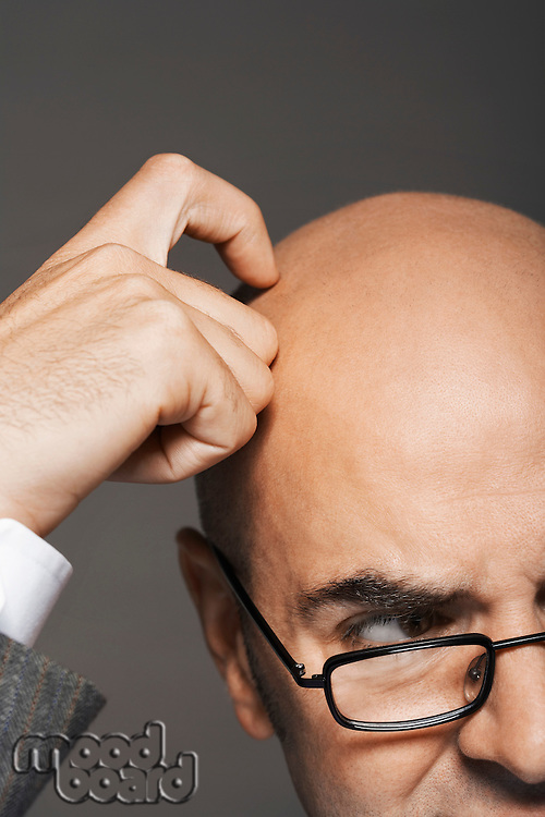 Bald businessman wearing glasses scratching head high section