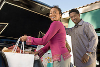 Smiling Couple Putting Shopping Bags into Trunk