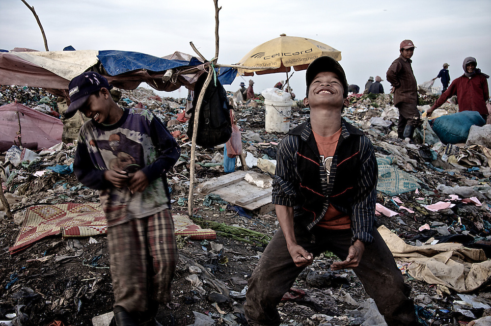 When unable to provide for themselves and their children, most humans will seek any means necessary to do so. Even when conditions are entirely undesirable.  Stung Meanchey garbage dump in Phnom Penh, Cambodia offers it's unwanted contents to those without other recourse.  Despairing souls stream in from the city and countryside alike for their chance to capture some of it's valuables and exchange them for money and basic daily nutrition.  Though the scene is unpleasant to be sure, it does not break the ever resilient spirit of the Khmer people. Smiles and joy are to be found simply by scratching the surface. The people there should become unexpected teachers to us all, that peace and contentment are found wholly within and can be delivered on demand, even in the face of external circumstances that logically summon the opposite.