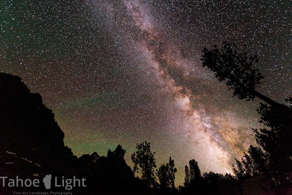 Milky Way galaxy rising through the forest at Saddlerock Lake just below Bishop Pass in the High Sierra mountain range in California.