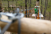 Chuck Fries, Park Manager at Bristol Mountain's new Aerial Adventure Park, crosses an obstacle on Tuesday, May 20, 2014.
