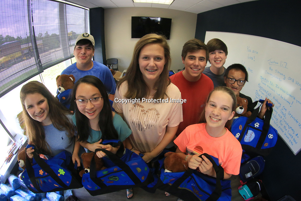 Teens Alaina Weeks, Noah Barnes, Abigail Moeller, Claire Blassingame, Jake Nelson, Katie Simpson, Ben Blassingame and Qiao Moeller pose with their hand-decorated supply bags and teddy bears which will go to children in foster care as part of the Together We Rise program.