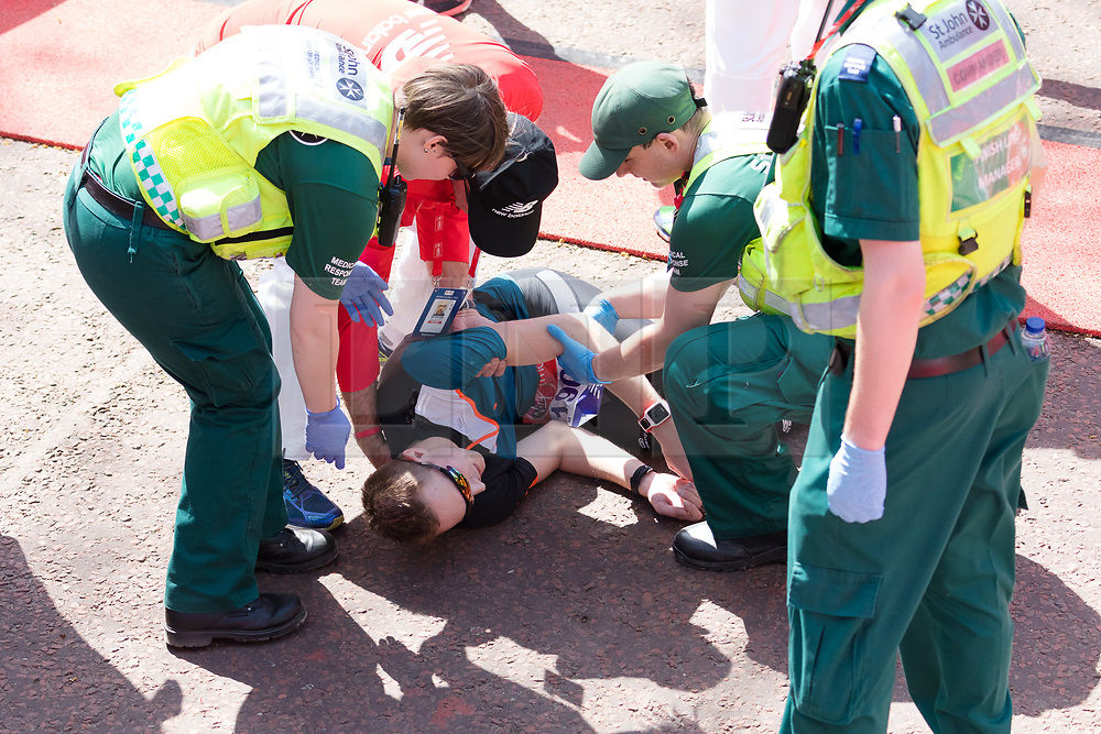 © Licensed to London News Pictures. 22/04/2018. London, UK. Runners collapse and receive medical assistance at the finish of the 2018 London Marathon. Photo credit: Vickie Flores/LNP